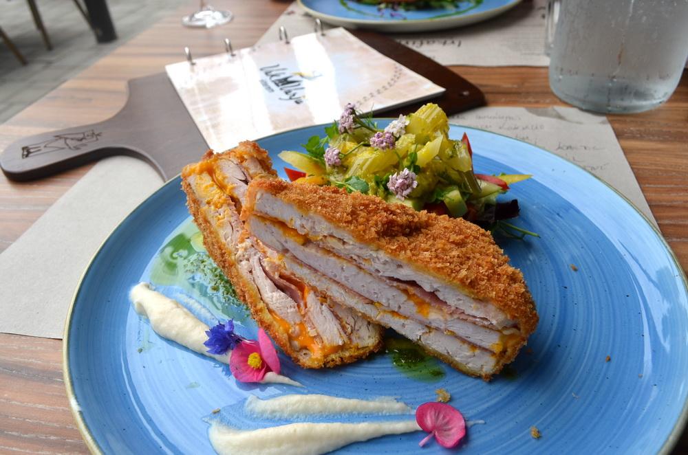 Cheddar sajttal töltött csirkemell érlelt sonkával, paszternákpürével és friss salátákkal a VakVarjú Csónakház éttermében. GasztroMagazin 2018.