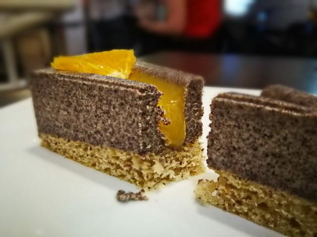 Narancsos máktorta az első. Esztétikus, illatos, finom a folyékony töltelékkel töltött tortaszelet.