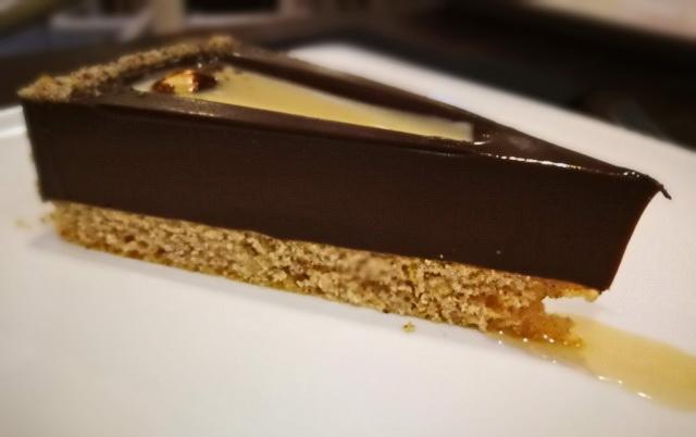 Tonkababbal bolondított csokoládétorta, karamellel és mogyoróval töltve. Kettévágva a szeletet, kifolyik a töltelék.Látványos, izgalmas megoldás.